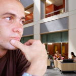 Wistful Alum Stares Longingly at Table in Duffield Where They Once Hit Rock Bottom